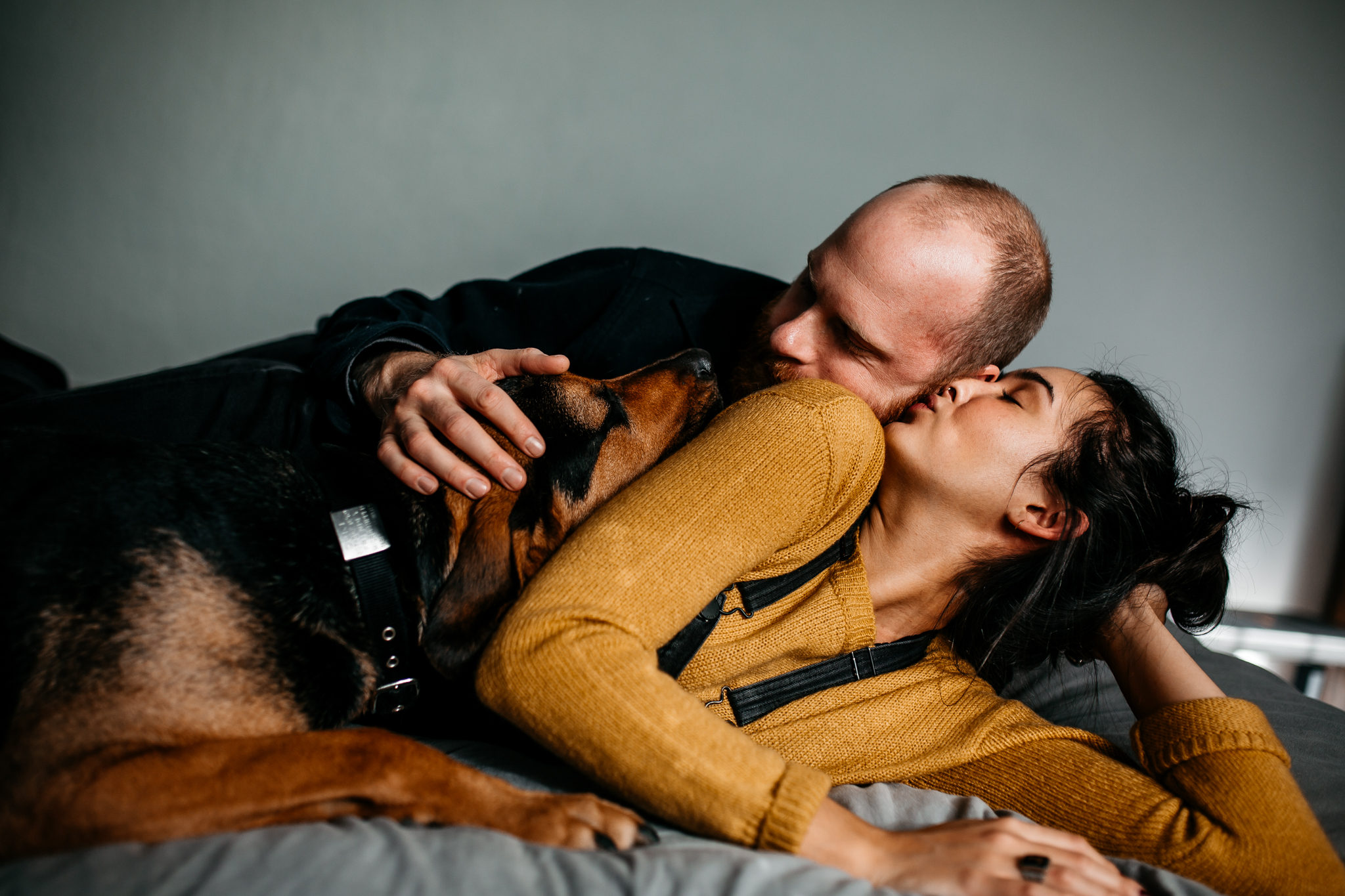 colorado documentary photographer - image of a couple and their hound dog laying in bed together